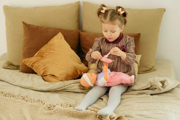petite fille qui donne à manger à sa poupée